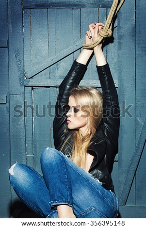 Portrait of one attractive sensual sexy young serious passionate blonde woman with long hair in leather black jacket and jeans with raised hands in rope on wooden background, vertical picture - stock photo