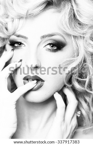 Portrait of one beautiful sensual sexy young retro blonde woman with curly hair and bright makeup looking forward holding hands near face black and white closeup, vertical picture