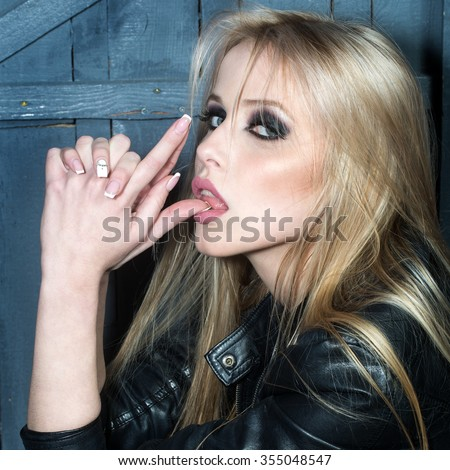Portrait of one beautiful sensual sexy young serious passionate blonde woman with long hair in leather black jacket holding hands as gun in studio on wooden wall background, vertical picture