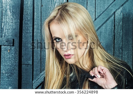 Portrait of one beautiful sensual sexy young serious passionate blonde woman with long hair in leather black jacket in studio on wooden wall background, horizontal picture