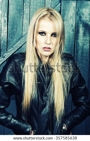 Portrait of one beautiful sensual sexy young serious passionate blonde woman with long hair in leather black jacket in studio on wooden wall background, vertical picture