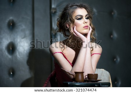Portrait of one beautiful sexy sensual young woman with bright makeup and curly hair in red dress near column holding coffee cup sitting in studio on leather black background, horizontal picture