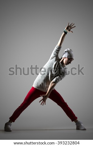 Portrait of one handsome fit young man dancing, working out wearing casual red pants and hat. Modern style cool dancer guy training. Full length photo image on studio gray background - stock photo