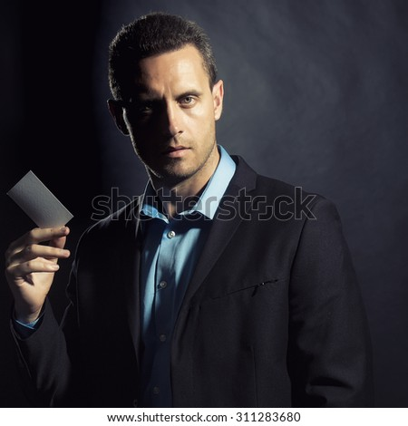 Portrait of one handsome sexual unshaven young business man in jacket and blue shirt holding white calling card in hand looking forward standing on black studio background copyspace, square picture - stock photo