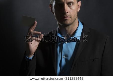 Portrait of one handsome sexual unshaven young man in jacket and blue shirt holding white business card in hand looking forward standing on black studio background copyspace, horizontal picture - stock photo