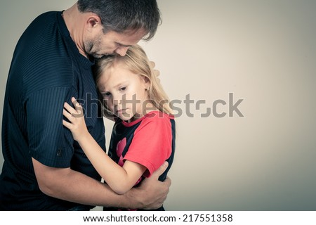 portrait of one sad daughter hugging her father - stock photo