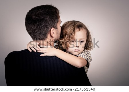 portrait of one sad son hugging his father - stock photo