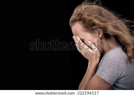 portrait of one sad woman standing near a wall and holding her head in her hands