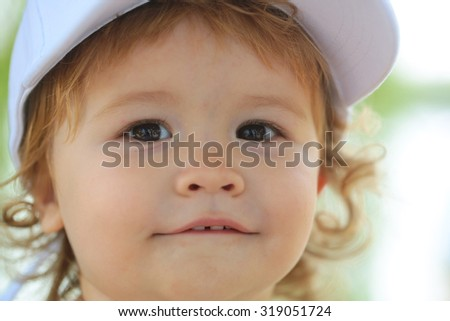 Portrait of one small happy smiling male kid swith blond curly hair in white cap on green natural blur background closeup, horizontal picture - stock photo