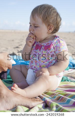 portrait of one year baby eating banana on towel next to mom at beach - stock photo