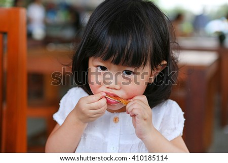 Portrait of one year old and eight month child, Baby girl eating a chicken wing - stock photo