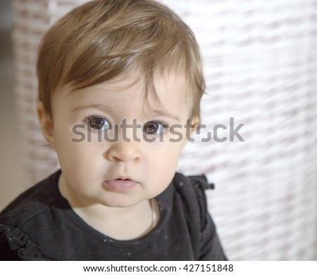 Portrait of one year old baby with brown eyes looking calmly at camera