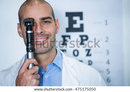 Portrait of optometrist looking through ophthalmoscope in ophthalmology clinic