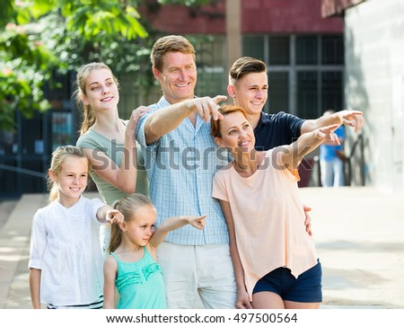 Portrait of ordinary large family of six standing pointing with finger together outdoors