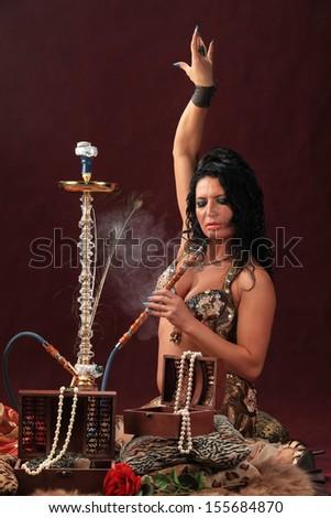 young woman inhaling hookah girl smoking shisha lying on