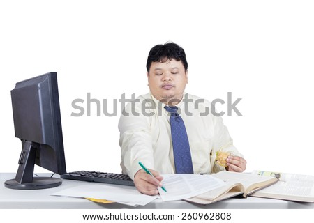 Portrait of overweight manager working on table while eating burger and write on paper - stock photo
