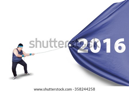Portrait of overweight person wearing sportswear and pulling a big flag with numbers 2016 in the studio - stock photo