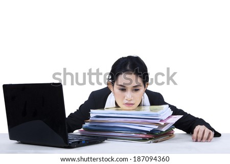 Portrait of overworked business woman take a rest on a pile of documents