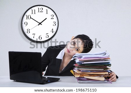 Portrait of overworked businesswoman take a rest on a pile of documents - stock photo