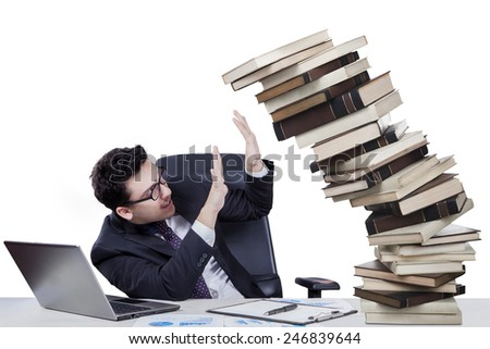 Portrait of overworked young businessman holds falling books on the desk - stock photo