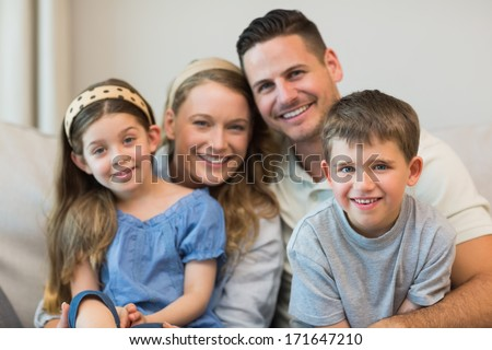 Portrait of parents and children sitting on sofa at home - stock photo