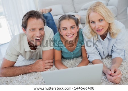 Portrait of parents and daughter using a laptop lying on a carpet - stock photo