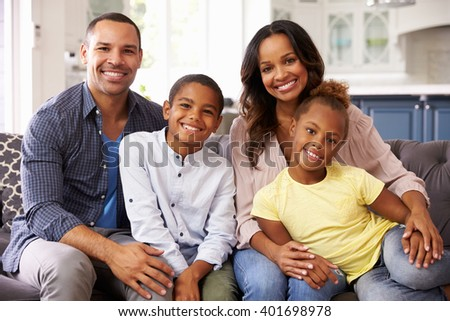Portrait of parents and young children relaxing at home - stock photo