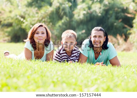 Portrait of  parents with teenager in grass at park