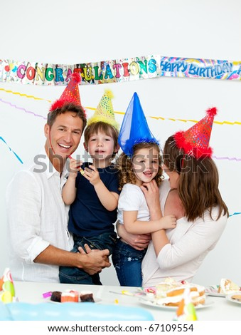 Portrait of parents with their children during a birthday party at home - stock photo