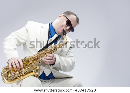 Portrait of Passionate Expressive Male Alto Saxophone Player in White Suit. Posing Against White Background. Horizontal Image Orientation - stock photo