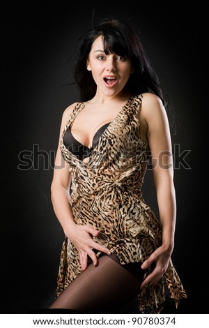 Portrait of passionate young woman in tiger dress with deep neckline on dark background in studio - stock photo