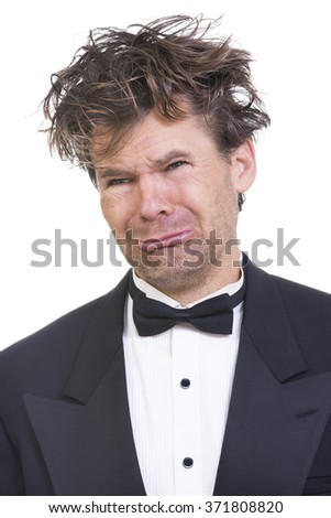Portrait of pathetic crying Caucasian man with long messy hair wearing flashy black tuxedo on white background - stock photo