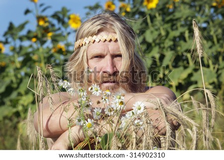 portrait of peasant in a field of sunflowers, get tired from work in summer day - stock photo