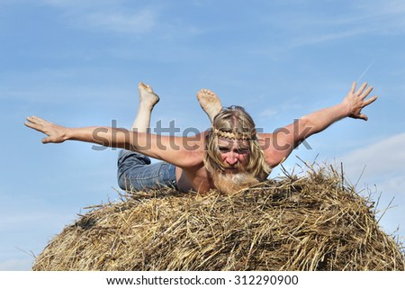portrait of peasant in a field on a haystack in summer day - stock photo