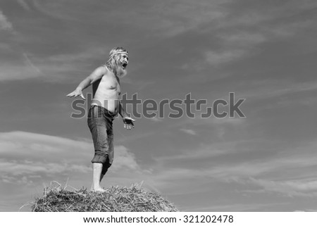 portrait of peasant in a field on a haystack in summer day, bw - stock photo