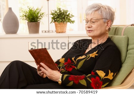 Portrait of pensioner reading in armchair in bright living room.?