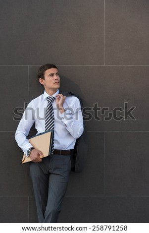 Portrait of pensive and confident adult businessman, wearing suit and necktie with documents in front of gray wall with copyspace - stock photo