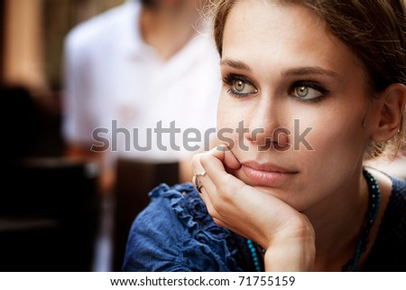 Portrait of pensive beautiful woman in the city - stock photo