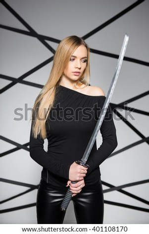Portrait of pensive blond woman posing with sword - stock photo