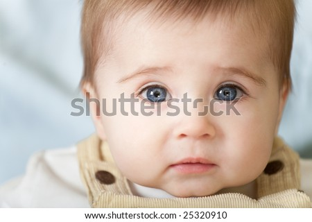 Portrait of pensive blue-eyes baby. Face close-up - stock photo