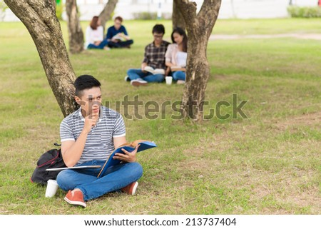 Portrait of pensive college student sitting on campus with a textbook - stock photo