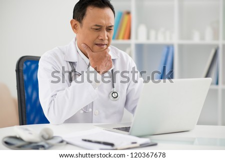 Portrait of pensive doctor sitting in his office and looking at laptop - stock photo