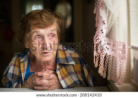 Portrait of pensive elderly woman looking out the window. - stock photo