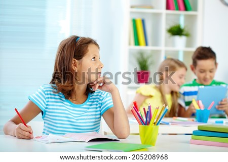 Portrait of pensive girl drawing at workplace with her schoolmates on background - stock photo