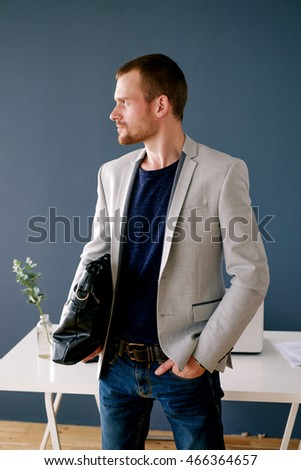 Portrait of pensive good-looking man in elegant clothes with bag and hand in pocket looking pensively away