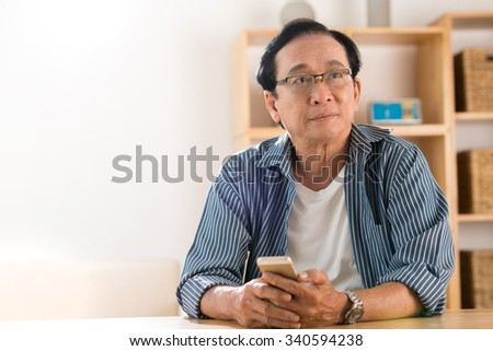 Portrait of pensive man with a smartphone trying to remember telephone number - stock photo