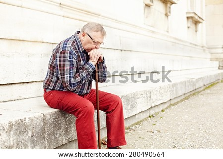 Portrait of pensive mature man in glasses and plaid shirt resting leaning on his wooden walking stick - stock photo