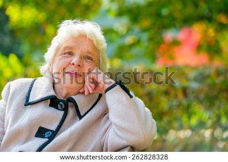 Portrait of pensive older ladies in a coat - stock photo