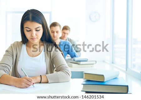 Portrait of pensive student carrying out test at lesson - stock photo