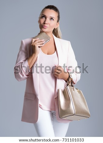 Portrait of pensive woman with purse in hand and a handbag in hands over white background